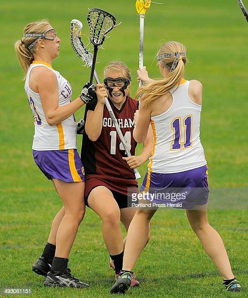 Meghan Cushing of Gorham splits her way through Cheverus defenders Alex Logan left and Mary Kate Slattery right during a girls' lacrosse game...