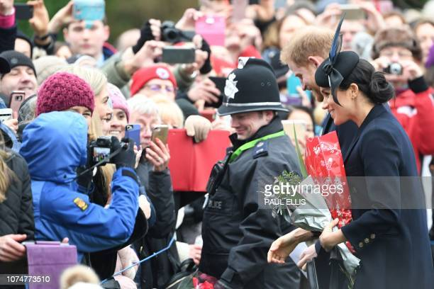 Meghan Duchess of Sussex and Britain's Prince Harry Duke of Sussex greet the crowds as they depart after the Royal Family's traditional Christmas Day...
