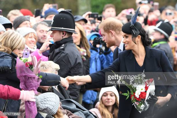 Meghan, Duchess of Sussex and Britain's Prince Harry, Duke of Sussex greet the crowds after the Royal Family's traditional Christmas Day service at...