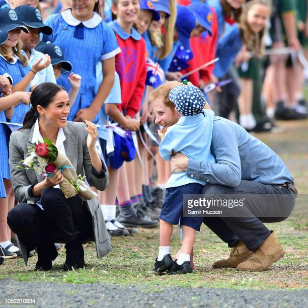 Meghan Duchess of Sussex and Prince Harry Duke of Sussex greet a young boy as they arrive at Dubbo Airport on October 17 2018 in Dubbo Australia The...