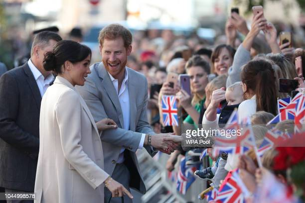 Meghan, Duchess of Sussex and Prince Harry, Duke of Sussex greet well-wishers as they arrive for an engagement at Edes House during an official visit...