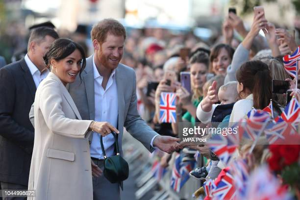 Meghan Duchess of Sussex and Prince Harry Duke of Sussex greet wellwishers as they arrive for an engagement at Edes House during an official visit to...