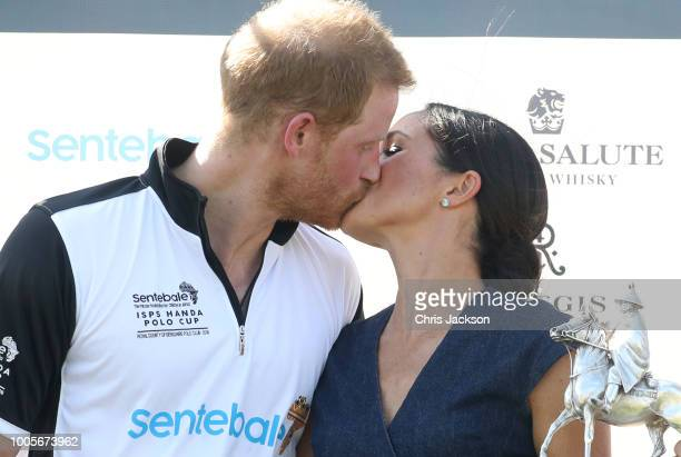 Meghan Duchess of Sussex and Prince Harry Duke of Sussex kiss after posing with the trophy after the Sentebale Polo 2018 held at the Royal County of...