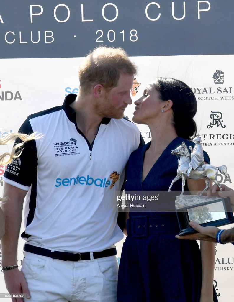 Meghan, Duchess of Sussex and Prince Harry, Duke of Sussex kiss as they pose with the trophy after the Sentebale ISPS Handa Polo at the Royal County of Berkshire Polo Club on July 26, 2018 in Windsor, England.