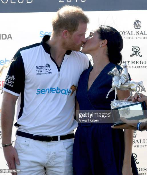 Meghan Duchess of Sussex and Prince Harry Duke of Sussex kiss as they pose with the trophy after the Sentebale ISPS Handa Polo at the Royal County of...