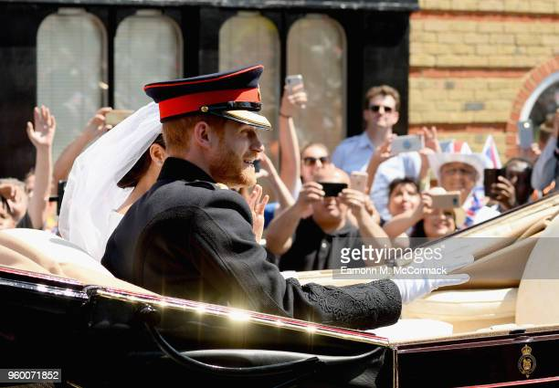 Meghan Duchess of Sussex and Prince Harry Duke of Sussex leave Windsor Castle in the Ascot Landau carriage during a procession after getting married...