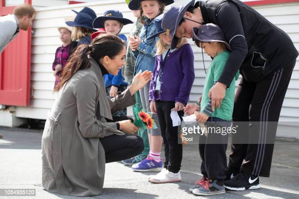 Meghan Duchess of Sussex and Prince Harry Duke of Sussex meet children during a visit to Marenui Cafe on October 29 2018 in Wellington New Zealand...