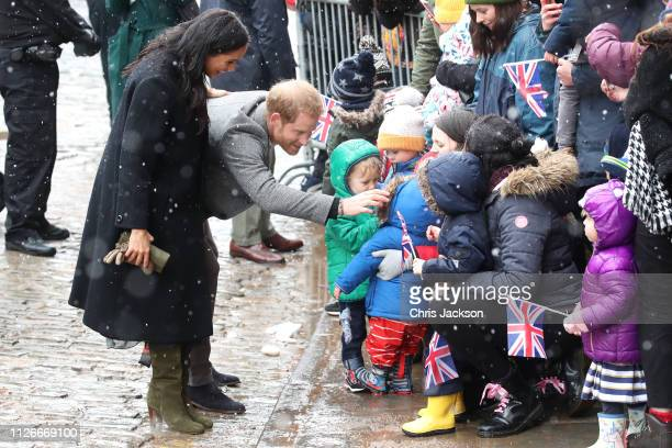 Meghan Duchess of Sussex and Prince Harry Duke of Sussex meet children in the crowd as they arrive at the Bristol Old Vic on February 01 2019 in...