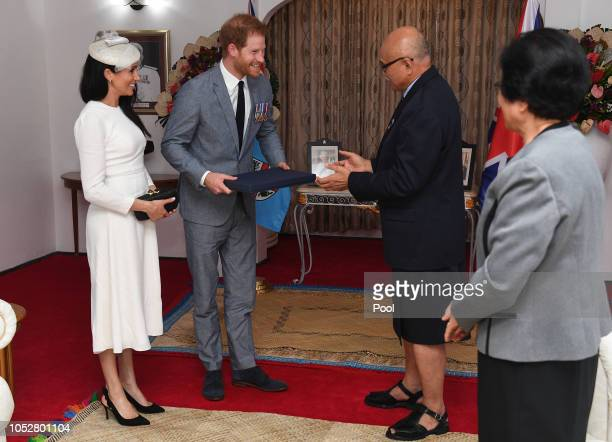 Meghan Duchess of Sussex and Prince Harry Duke of Sussex present a gift to the President of Fiji Jioji Konrote as his wife Sarote Faga Konrote looks...
