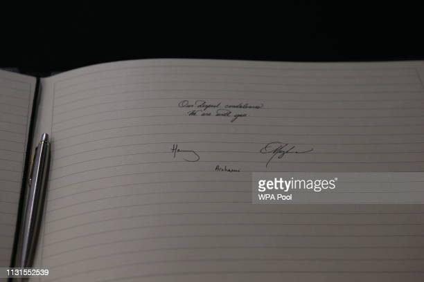 Meghan Duchess of Sussex and Prince Harry Duke of Sussex sign a book of condolence on behalf of The Royal Family at New Zealand House on March 19...