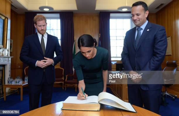 Meghan Duchess of Sussex and Prince Harry Duke of Sussex sign the visitors book in the office of the Taoiseach Leo Varadkar at the start of a twoday...