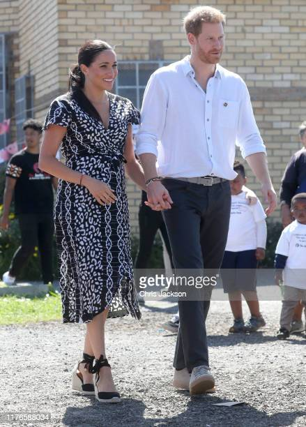 Meghan, Duchess of Sussex and Prince Harry, Duke of Sussex smile as they visit a Justice Desk initiative in Nyanga township, during their royal tour...