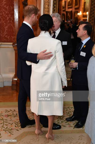 Meghan Duchess of Sussex and Prince Harry Duke of Sussex speak to Simon Weston and Alun Cairns as they attend a reception to mark the fiftieth...