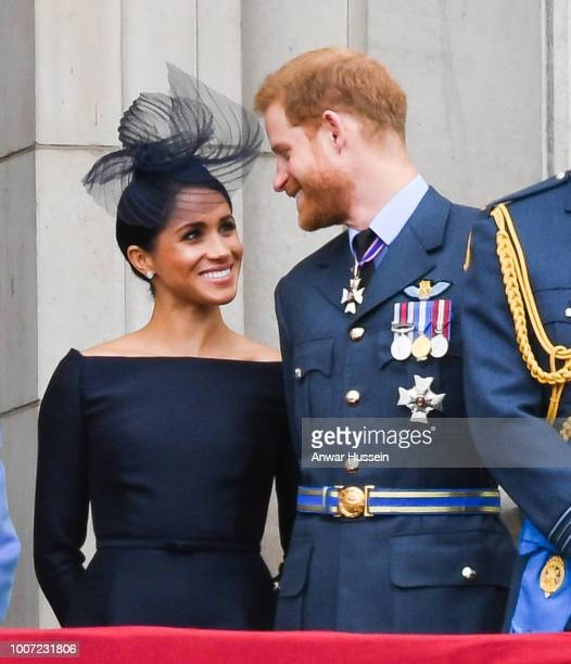 Meghan Duchess of Sussex and Prince Harry Duke of Sussex stand on the balcony of Buckingham Palace to view a flypast to mark the centenary of the...
