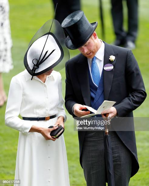 Meghan Duchess of Sussex and Prince Harry Duke of Sussex study a race card as they attend day 1 of Royal Ascot at Ascot Racecourse on June 19 2018 in...