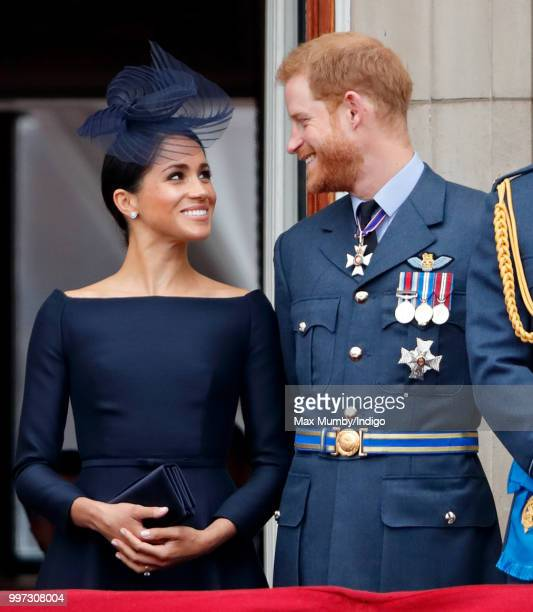 Meghan Duchess of Sussex and Prince Harry Duke of Sussex watch a flypast to mark the centenary of the Royal Air Force from the balcony of Buckingham...