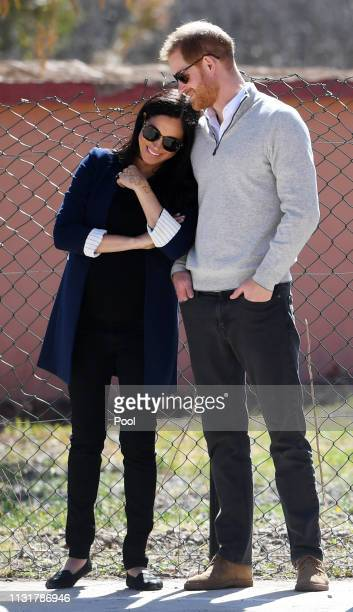 Meghan Duchess of Sussex and Prince Harry Duke of Sussex watch students play football during their visit to Lycée Qualifiant Grand Atlas the local...