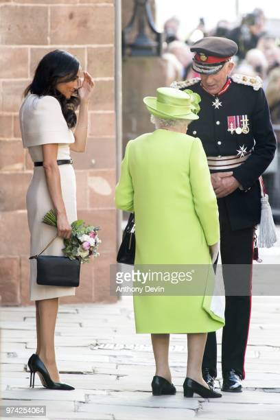 Meghan Duchess of Sussex and Queen Elizabeth II speak with the Lord Lieutenant as they leave Chester Town Hall on June 14 2018 in Chester England...