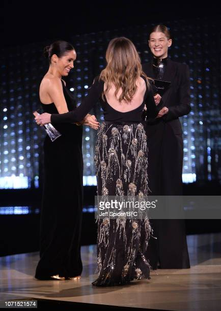 Meghan Duchess of Sussex and Rosamund Pike present the award for British Designer of the Year Womenswear Award to Clare Waight Keller for Givenchy...