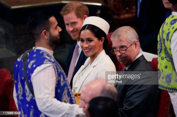 Meghan Duchess of Sussex between husband Prince Harry and Prince Andrew the Duke of York smiles as drummers perform during the Commonwealth Service...