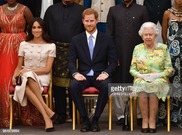 TOPSHOT Meghan Duchess of Sussex Britain's Prince Harry Duke of Sussex and Britain's Queen Elizabeth II pose for a picture during the Queen's Young...