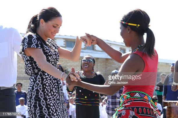 Meghan Duchess of Sussex dances as she visits a Justice Desk initiative in Nyanga township with Prince Harry Duke of Sussex during their royal tour...