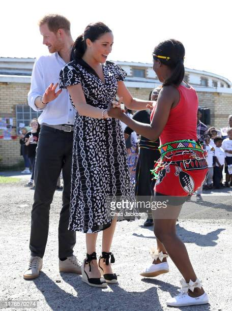 Meghan, Duchess of Sussex dances as she visits a Justice Desk initiative in Nyanga township, with Prince Harry, Duke of Sussex, during their royal...