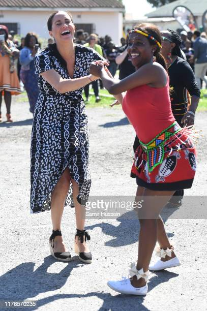 Meghan, Duchess of Sussex dances with locals as she visits a Justice Desk initiative in Nyanga township with Prince Harry, Duke of Sussex, during...