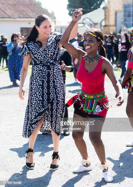 Meghan Duchess of Sussex dances with locals as she visits a Justice Desk initiative in Nyanga township with Prince Harry Duke of Sussex during their...