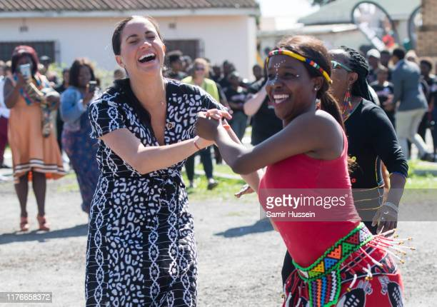 Meghan Duchess of Sussex dances with locals as she visits the Nyanga Township with Prince Harry Duke of Sussex during their royal tour of South...