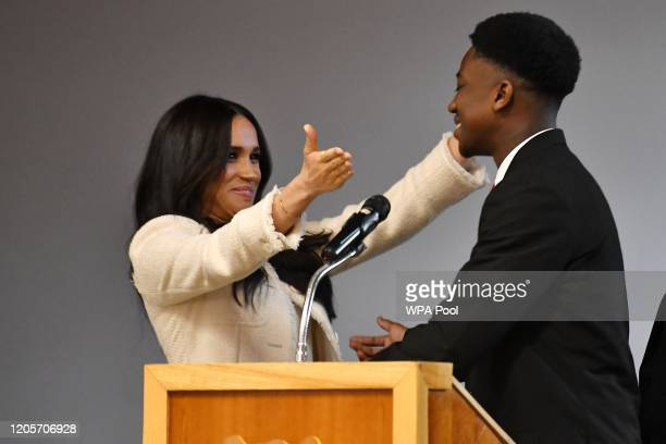 Meghan, Duchess of Sussex embraces student Aker Okoye during a special school assembly at the Robert Clack Upper School in Dagenham ahead of...