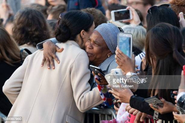 Meghan, Duchess of Sussex gets a hug from a member of the public during a visit to Edes House during an official visit to Sussex on October 3, 2018...