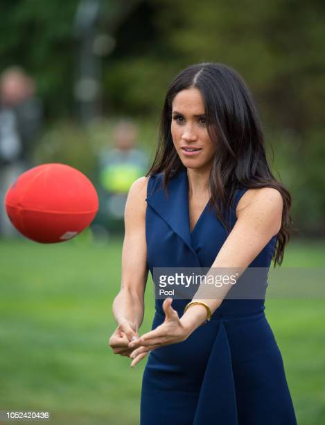 Meghan Duchess of Sussex handballs an Australian Rules football while watching a demonstration of sporting activities organised by the This Girl Can...