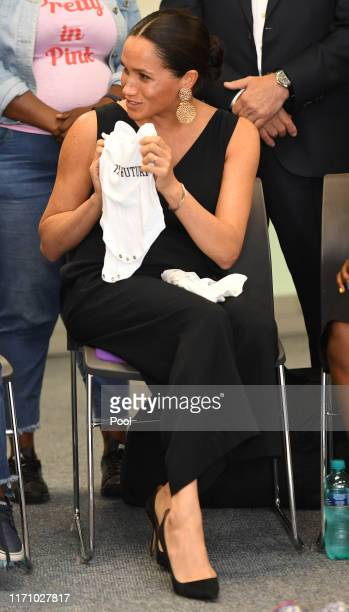 Meghan, Duchess of Sussex hands some of Archies clothes to the group as she visits mothers2mothers during her royal tour of South Africa with Prince...