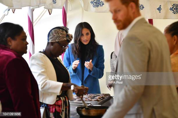 Meghan Duchess of Sussex helps to prepare food at an event to mark the launch of a cookbook with recipes from a group of women affected by the...