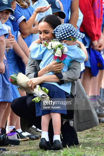 Meghan, Duchess of Sussex hugs a young boy as she arrives at Dubbo Airport on October 17, 2018 in Dubbo, Australia. The Duke and Duchess of Sussex...