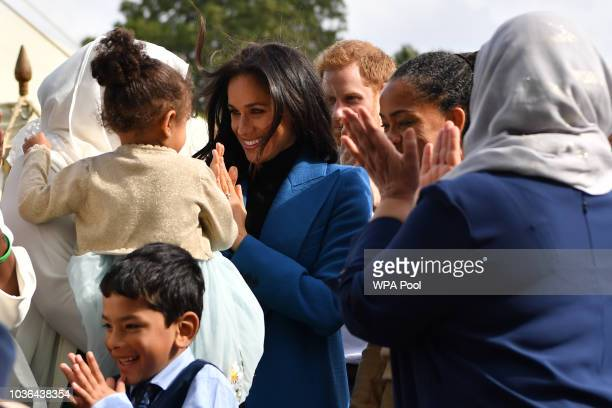 Meghan Duchess of Sussex interacts with a young girl as she gathers for a family photo at an event to mark the launch of a cookbook with recipes from...