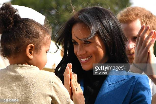 Meghan Duchess of Sussex interacts with a young girl at an event to mark the launch of a cookbook with recipes from a group of women affected by the...