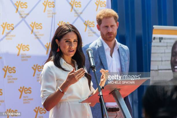 Meghan Duchess of Sussex is watched by Britain's Prince Harry Duke of Sussex as she delivers a speech at the Youth Employment Services Hub in Tembisa...