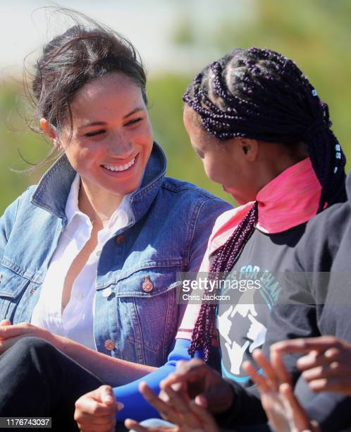Meghan Duchess of Sussex join surf mentors and participate in a group activity to promote positive thinking with Prince Harry Duke of Sussex as they...