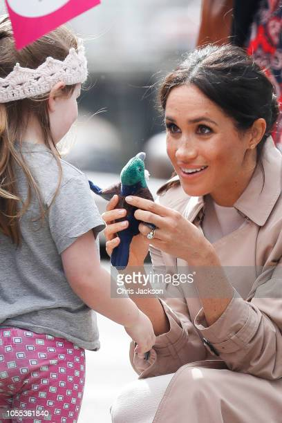 Meghan Duchess of Sussex kneeling down to talk to a young girl during 'Walkabout' on October 30 2018 in Auckland New Zealand The Duke and Duchess of...