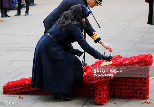 Meghan Duchess of Sussex lays a Cross of Remembrance in front of wooden crosses from the Graves of Unknown British Soldiers from the First and Second...