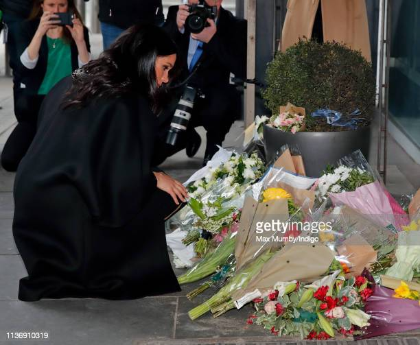 Meghan Duchess of Sussex lays flowers during a visit to New Zealand House to sign a book of condolence on behalf of The Royal Family following the...