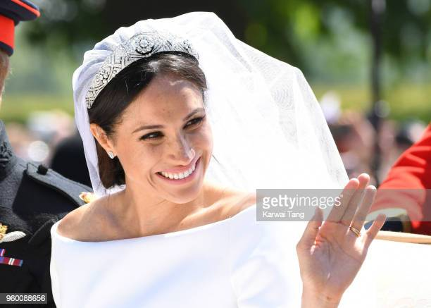 Meghan, Duchess of Sussex leaves Windsor Castle in the Ascot Landau carriage during a procession after getting married at St Georges Chapel on May...