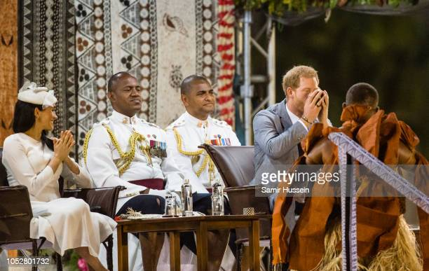Meghan Duchess of Sussex looks on as Prince Harry Duke of Sussex Harry takes a sip of Kava the national drink of Fiji during official welcome...