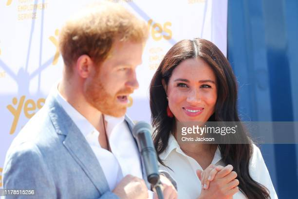 Meghan, Duchess of Sussex looks on as Prince Harry, Duke of Sussex speaks during a visit a township to learn about Youth Employment Services on...