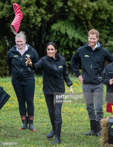Meghan Duchess of Sussex participates in wellie wanging as Prince Harry Duke of Sussex looks on during a visit to the North Shore to dedicate a...