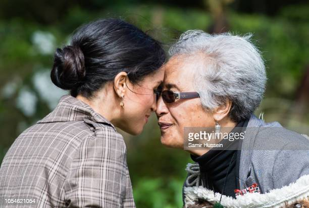Meghan, Duchess of Sussex performs a hongi as she attends a traditional welcome ceremony on the lawns of Goverment House on October 28, 2018 in...