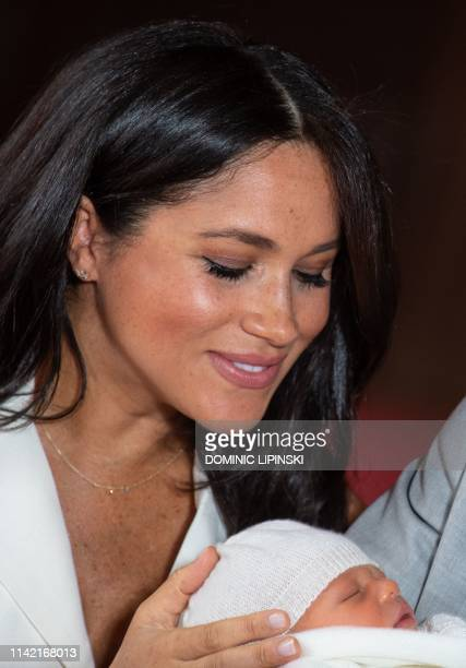 Meghan Duchess of Sussex places her hand on the head of her newborn baby boy as she and her husband Britain's Prince Harry Duke of Sussex pose for a...