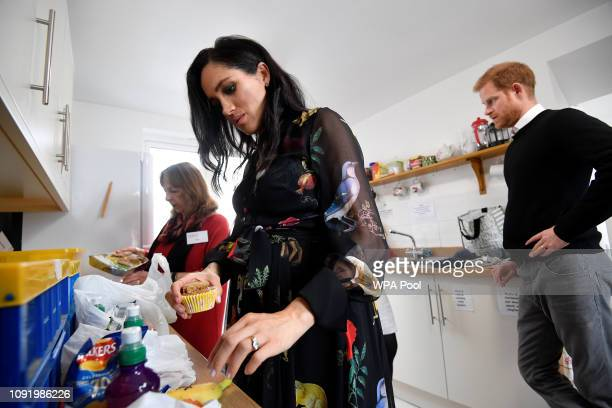 Meghan Duchess of Sussex prepares food parcels to go in the charity outreach van and writes personalised messages on fruit in the charity kitchen...
